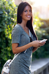 Smiling beautiful woman texting with her phone in the garden.