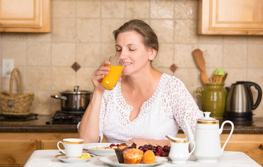 Middle aged woman having breakfast in a kitchen of her house