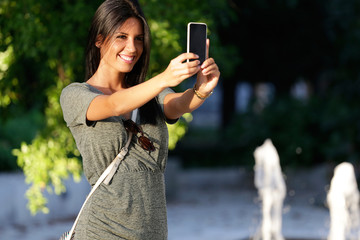 Happy beautiful girl taking a selfie photo in park.