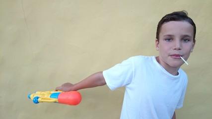 Niño con piruleta y pistola de agua
