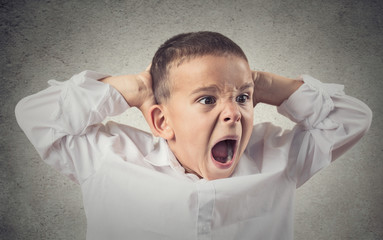 Portrait headshot Angry boy screaming, grey wall background