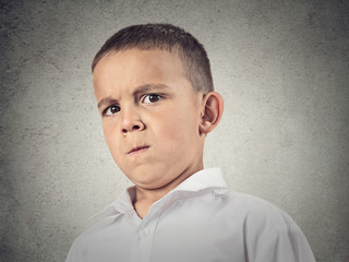 Suspicious boy, full of skepticism isolated grey wall background