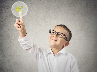 Boy touching yellow euro currency sign, grey wall background