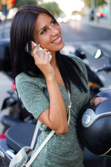 Beautiful girl sitting on a scooter and talking with phone.