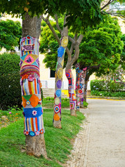 Yarn bombing in trees. European park.