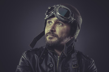 wartime pilot dressed in vintage style leather cap and goggles
