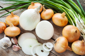 different onions and garlic on wooden table