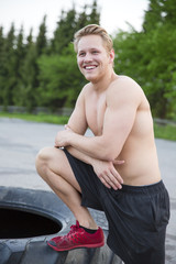 Smiling man with bare upper body rests outdoor