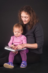 Pretty mother with daughter reading book