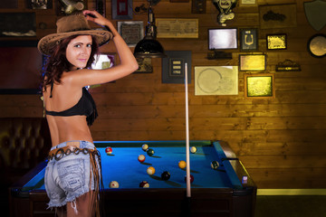 Close view of a beautiful cowgirl on a snooker club.