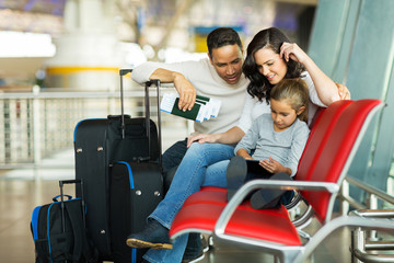 young girl with parents using tablet computer at airport