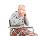 Senior man in wheelchair blowing his nose in a tissue