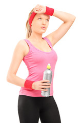 Exhausted athletic woman in sportswear holding a bottle of water