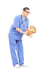 Full length portrait of a young male doctor giving a teddy bear