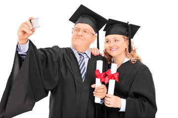 Mature male and female in graduation gowns taking a selfie