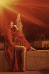 Retro looking photo of women in red dress sitting near fountain