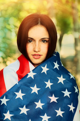 Calm young woman warp in US american flag