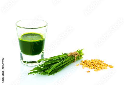 Shot glass of wheat grass with fresh cut wheat grass and wheat g - 68544938