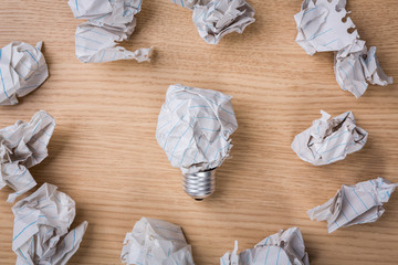 Crumpled paper Light bulb on wood background