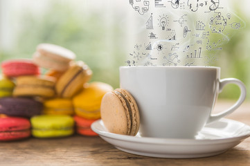 Coffee cup and French colorful macarons with business graph on s