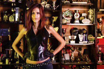 Biker girl standing in front of many trophies.