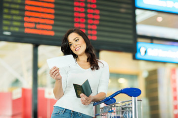 woman looking at air ticket in airport