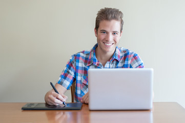 Young adult using computer and touch input tablet