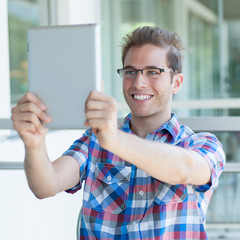 Young smiley male using a tablet pc