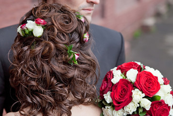 Wedding hairstyle with roses and bridal bouquet back view.