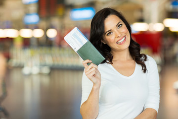 young woman holding passport and boarding pass