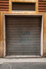 Saracinesche grigio zincane, negozio chiuso