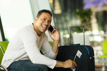 man talking on cell phone at airport