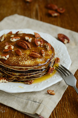 Stack of homemade thin pancakes topped with honey and pecan nuts