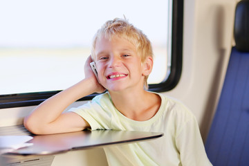 Young school boy talking on mobile phone sitting in train