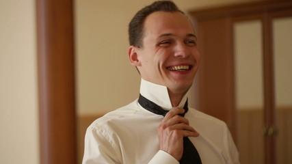Smiling Man Puts a Tie