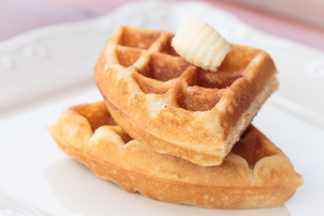 Waffle and butter on dish.
