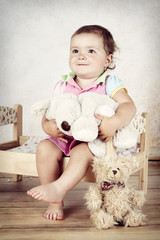Little girl sitting on the bed with plush toys
