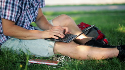 Student hands typing on laptop in the park