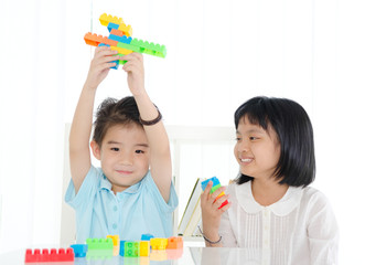 Asian kids piling up building blocks