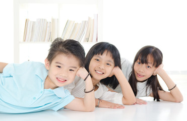 Asian kids lying on the floor and posing