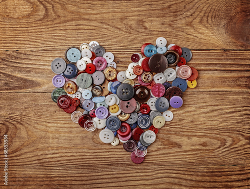 Colorful buttons heart on wood background
