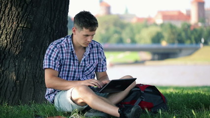 Young student working on laptop in city park