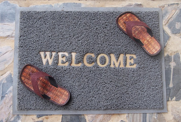 welcome mat with brown sandals on floor