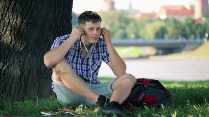 Young student listen to music on smartphone in city park