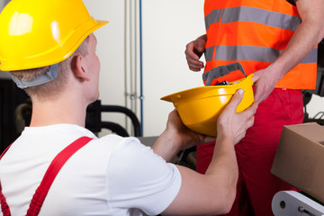 Male worker giving his colleague hardhat