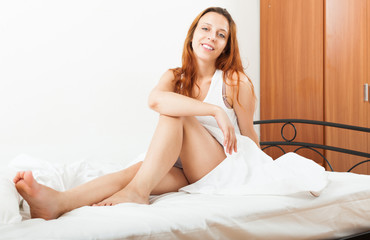 Long-haired woman waking in her bed with white sheets at home