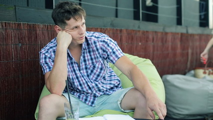 Sad, pensive man sitting in crowded outdoor cafe