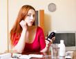 Sad red-haired young woman with medications in jar at home in li