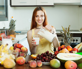 Happy woman pouring milk cocktail with fruits