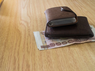 money in a brown wallet